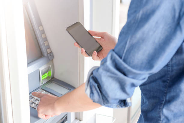 Man hand inserting a credit card in an atm - foto de stock