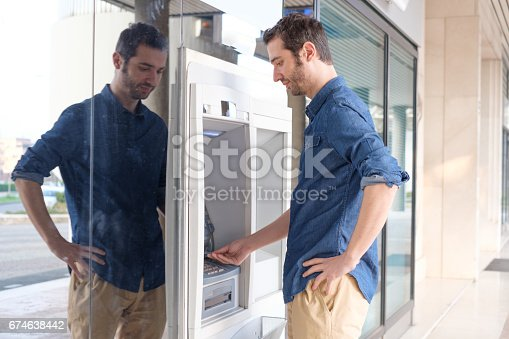 istock Man hand inserting a credit card in an atm 674638442