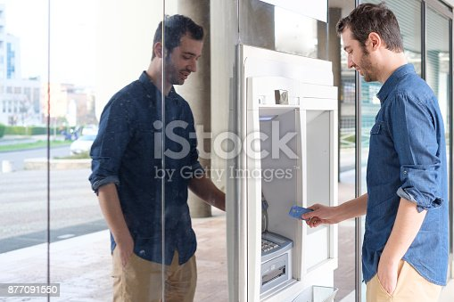 istock Man hand inserting a credit card in an atm 877091550