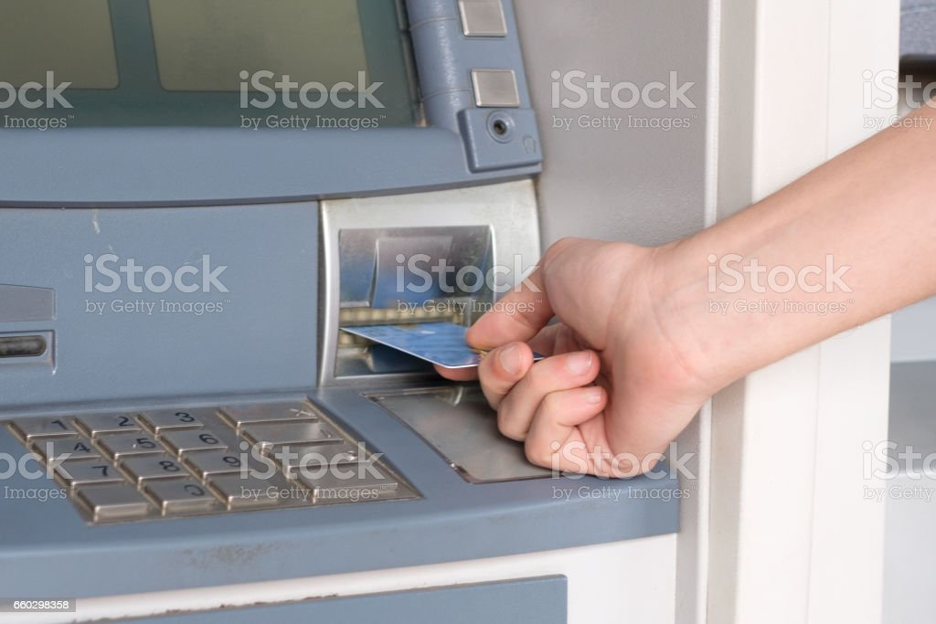 Man hand inserting credit card in an atm stock photo