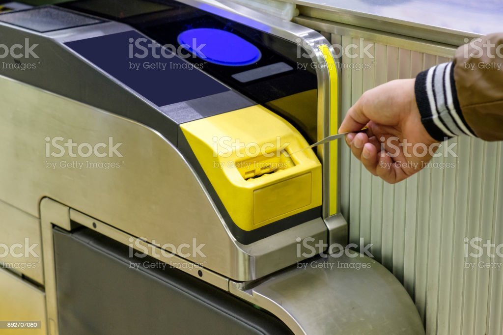 Man hand inserting ticket subway card in entrance stock photo