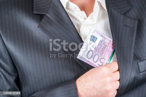 male hand hiding a bundle of money with par value of five hundred euros in the inside pocket of his jacket