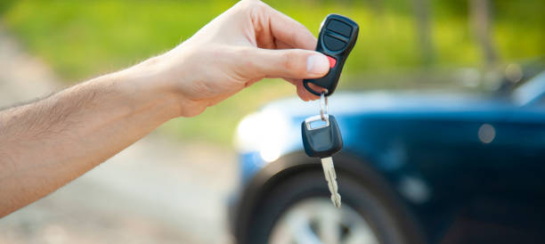 man hand key on car in nature stock photo
