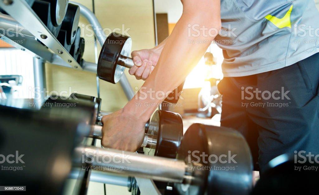 Man hand lifting dumbbells at gym stock photo