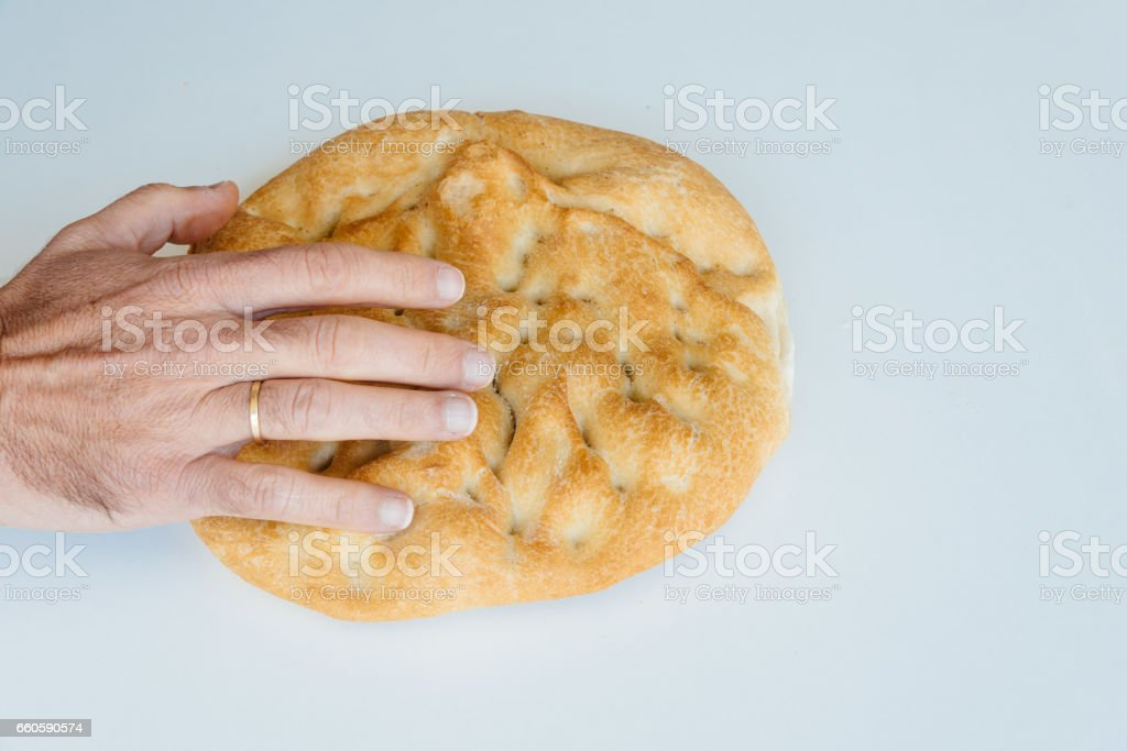 Man hand on loaf of bread on white table royalty-free stock photo