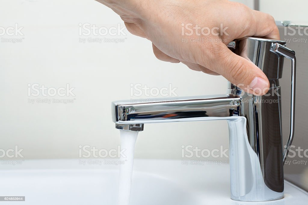 man hand on water tap stock photo
