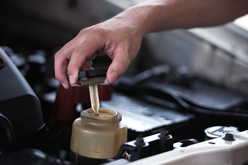 Man hand open power steering cap up for checking level of power steering fluid in the system, car maintenance service concept.