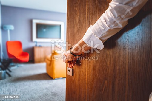 Toned man closing the door of the luxurious hotel room, man wearing a bracelet and a white shirt, closing the wooden door, nice and luxurious hotel room in the background.