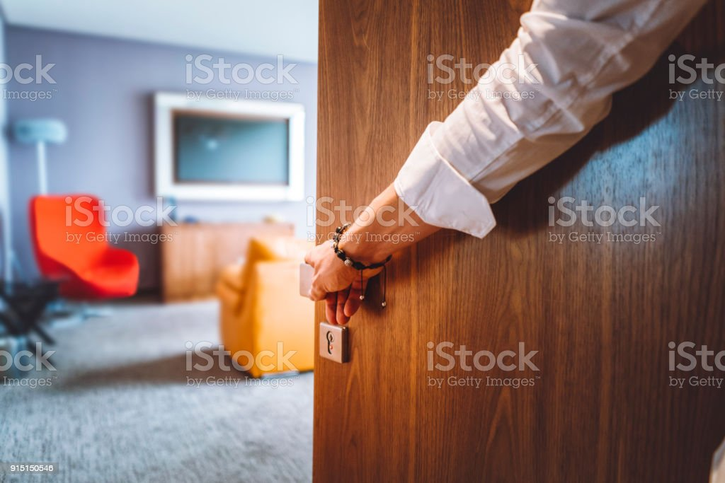Man hand opening the door of the luxurious hotel room stock photo