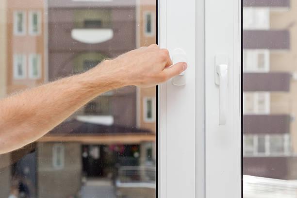 man hand opens a plastic pvc window - geglazuurd stockfoto's en -beelden