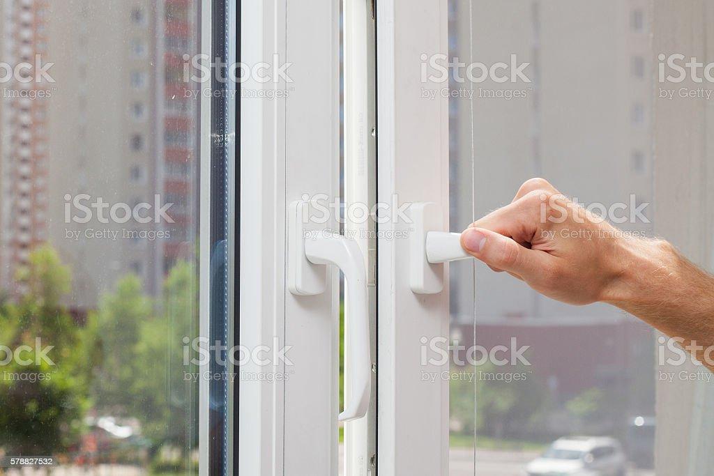 Man Hand opens a plastic pvc window stock photo