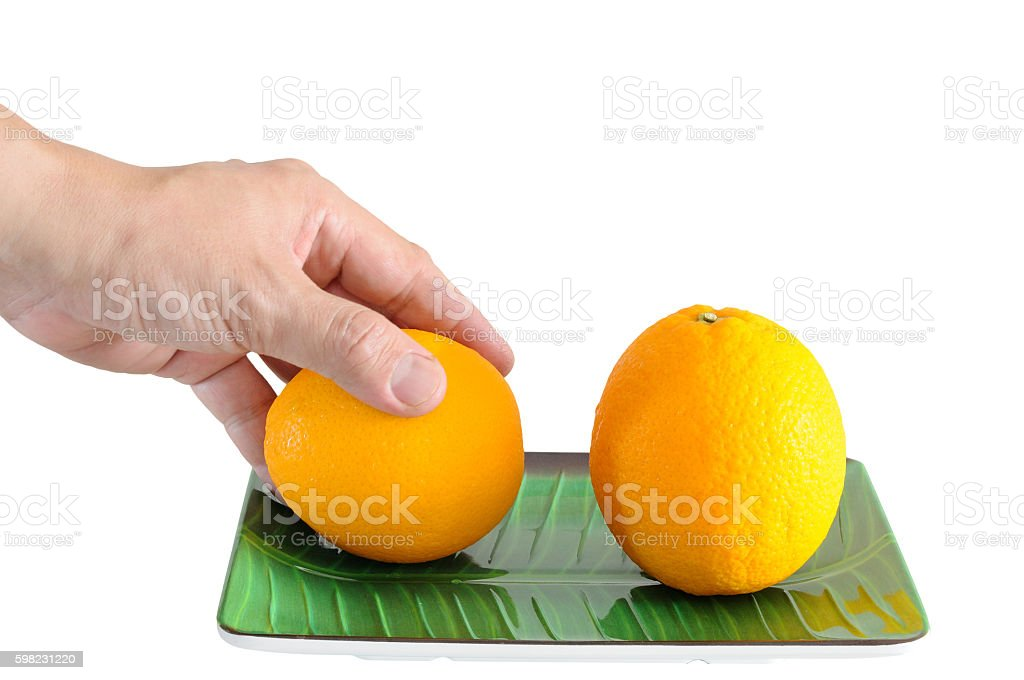 Man hand picking one oranges on plate isolated foto royalty-free