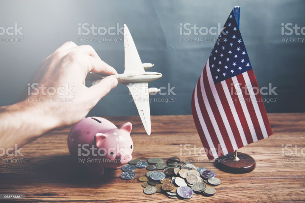 Man Hand Piggy Bank American Flag And Airplane Stock Photo