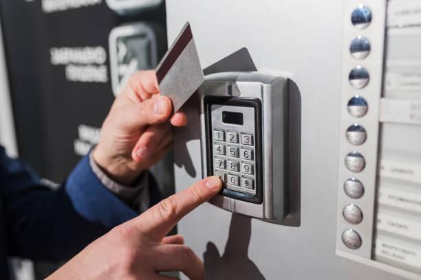 Hombre a mano presionando la combinación de código de seguridad y usando la tarjeta de acceso para desbloquear la puerta - foto de stock