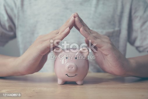 929887844 istock photo Man hand protect piggy bank on wood table. Save money and financial investment 1214408513