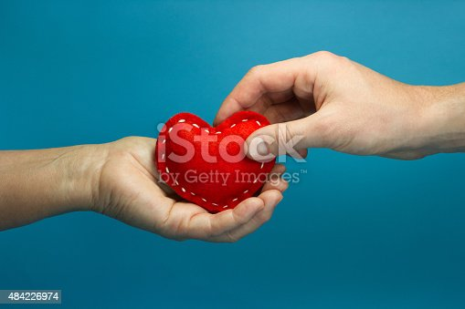 istock Man hand puting the red soft heart in woman hand 484226974