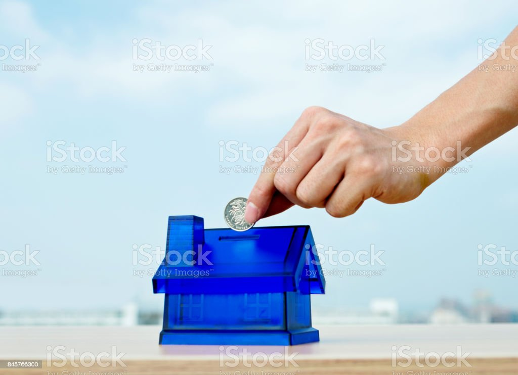 Man hand putting coin in to house shaped piggy bank stock photo