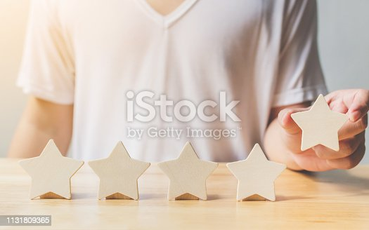 1133580311 istock photo A man hand putting wooden five star shape on table. The best excellent business services rating customer experience concept 1131809365