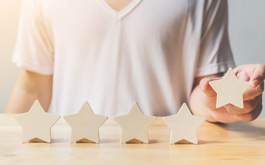 917079212 istock photo A man hand putting wooden five star shape on table. The best excellent business services rating customer experience concept 1131809365