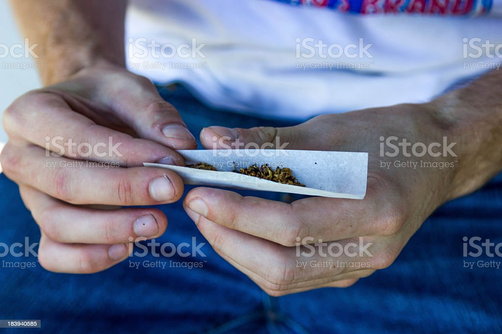 A man hand rolling a cigarette royalty-free stock photo
