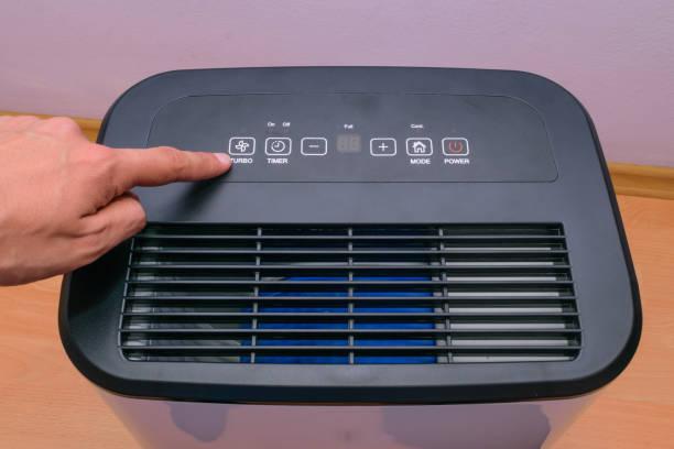 hand des mannes haus einrichten halten luftentfeuchter - luftfilter stock-fotos und bilder