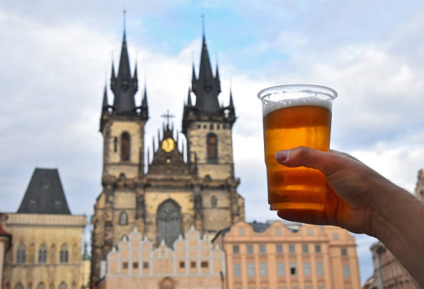 mão de homem mostrando o copo de cerveja ao longo da cidade de praga - praga boémia - fotografias e filmes do acervo