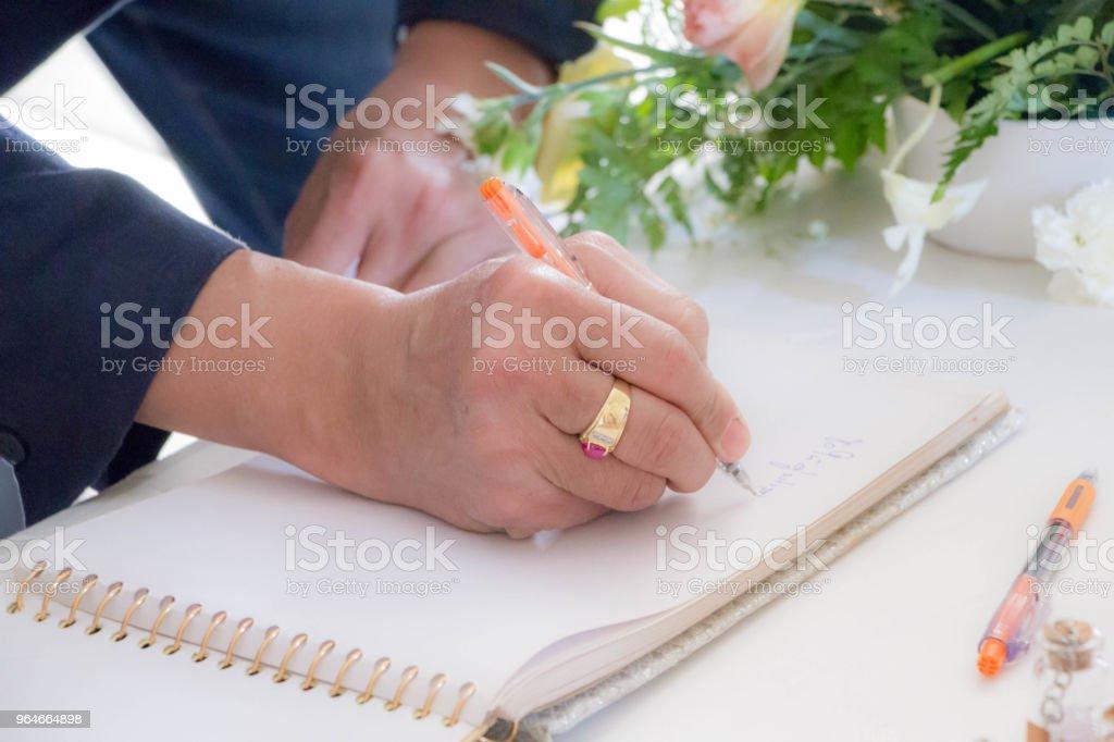 man hand signing a memory book royalty-free stock photo
