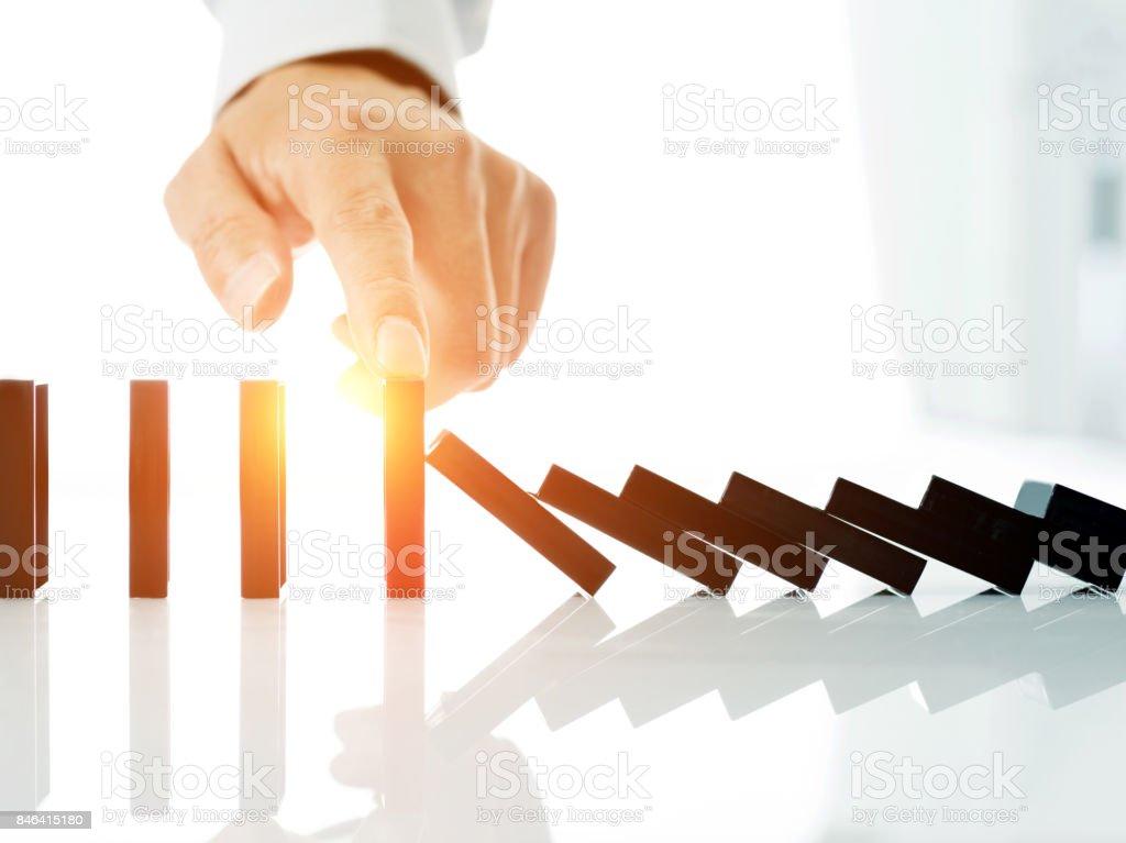 Man hand stop domino effect stock photo