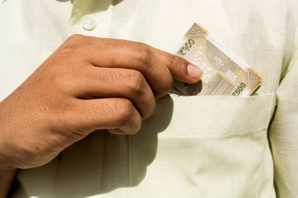 Man hand takes a new 500 indian currency note out of his pocket close up Man hand takes a indian currency out of his pocket close up depreciation stock pictures, royalty-free photos & images
