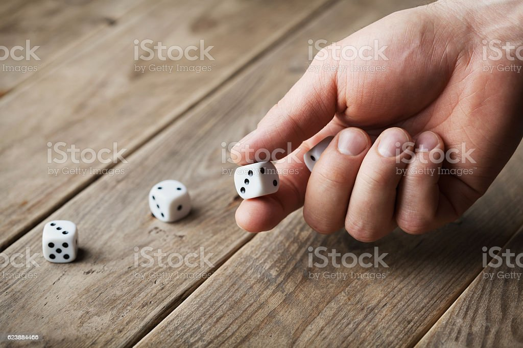 Man hand throwing dice. Gambling devices. Game of chance concept. stock photo