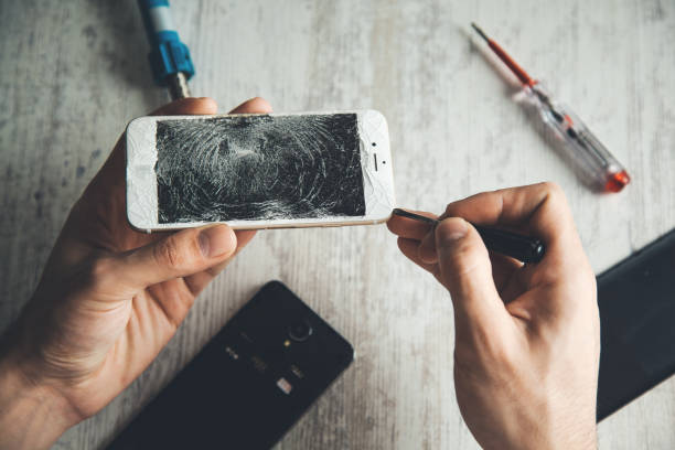 man hand tool with broken phone on table stock photo