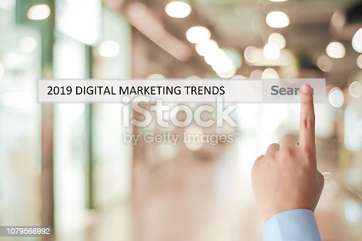istock Man hand touching 2019 digital marketing trends on search bar over blur office background, banner, 2019 business strategy annual plan, success in business concept 1079566992