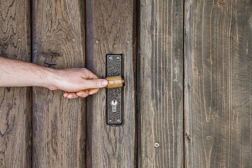 Man hand touching handle of old wooden door. Closeup.