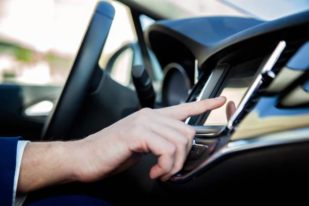 main de l'homme touchant l'écran lcd dans la voiture - écran tactile photos et images de collection