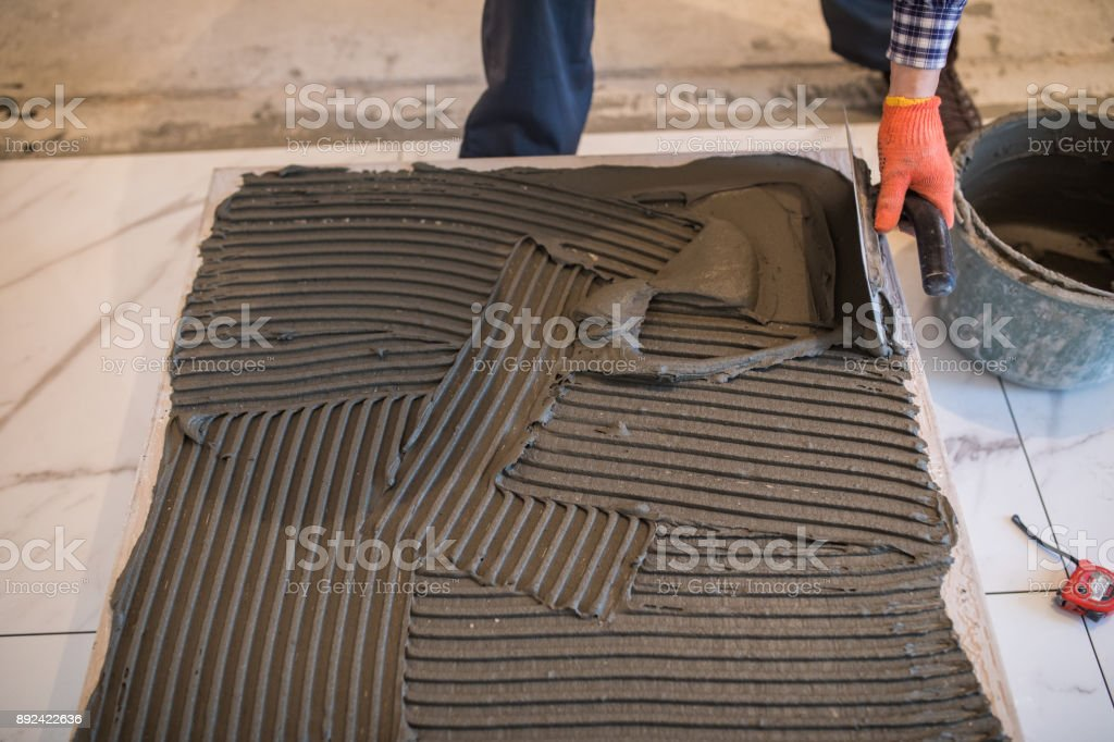 man hand troweling adhesive for ceramic tile flooring. Laying Ceramic Tiles. stock photo