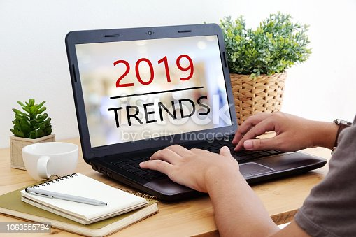 istock Man hand tying laptop computer with 2019 trends on screen background, digital marketing, business and technology concept 1063555794