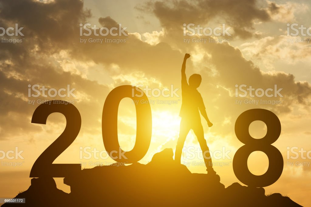 Man hand up on the peak of mountain and sunlight  with text 2018 sign happy new year calendar holiday concept stock photo