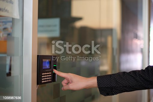 istock Man hand using biometric fingerprint scanner for track time to working. 1058987636