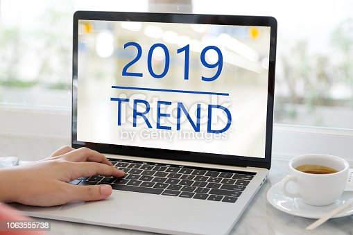 istock Man hand using laptop computer with 2019 trends on screen background, digital marketing, business and technology concept 1063555738