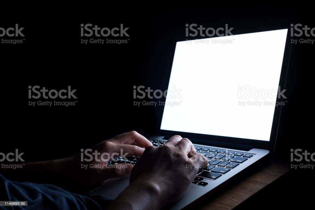 A man hand using laptop with blank screen at night. bedtime working...