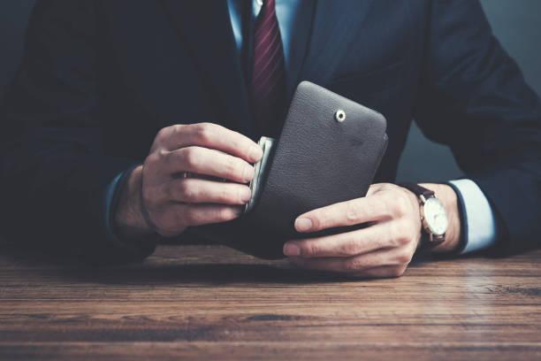 mann hand brieftasche und geld auf tisch - leder portemonnaie herren stock-fotos und bilder