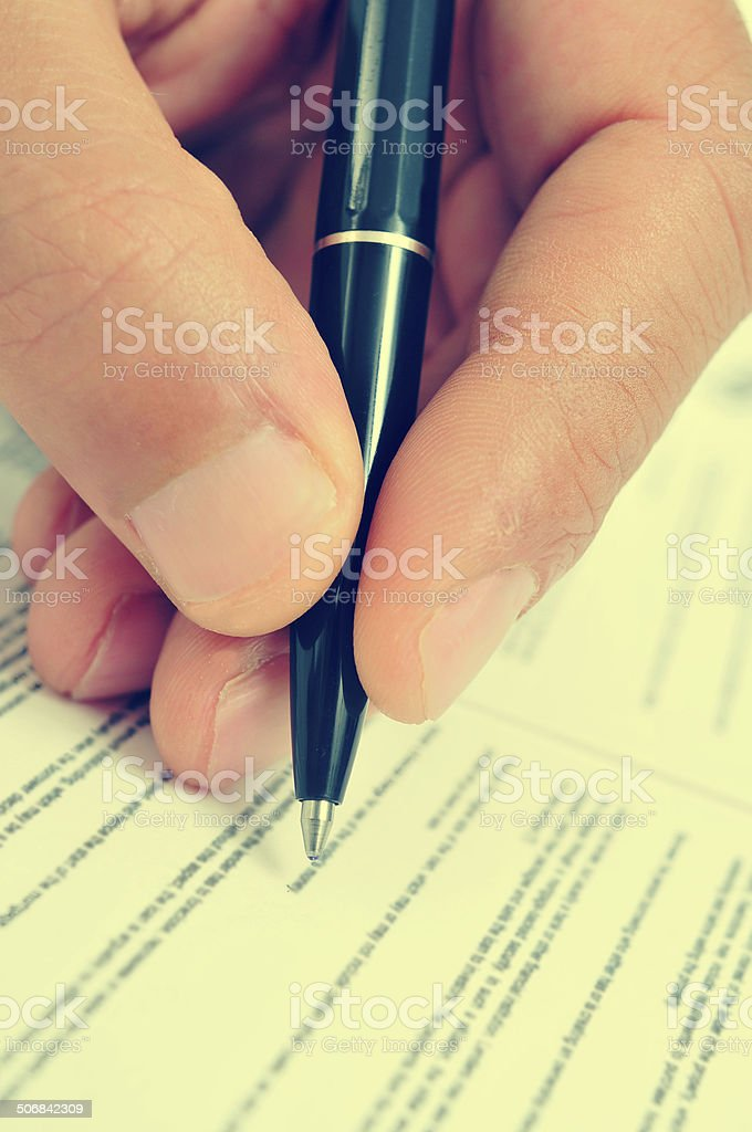 man hand with a pen, with a retro filter effect stock photo
