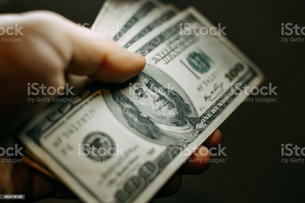 Man hand with a stack of hundred US dollars bills, close up stock photo
