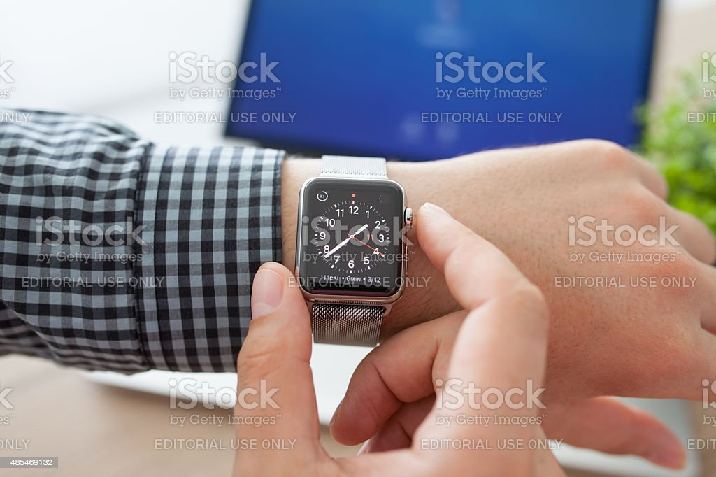 Man hand with Apple Watch and Macbook on the desk stock photo