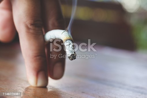 istock Man hand with burning cigarette as penis in smoking cause sexual erectile dysfunction,  tobacco causes to Erectile dysfunction 1146220061