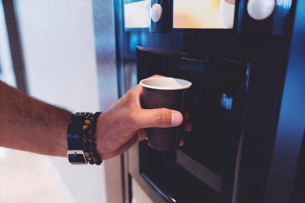 Man hand with coffee, vending coffee machine stock photo