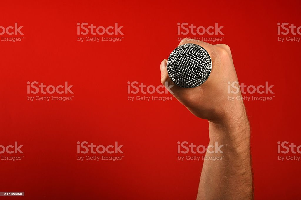 Man hand with microphone over red background royalty free stockfoto