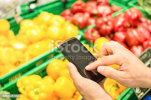 1184048369 istock photo Man hand with mobile smart phone at grocery store 530508380