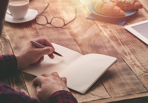 Man hand with pen writing on notebook on a wooden table