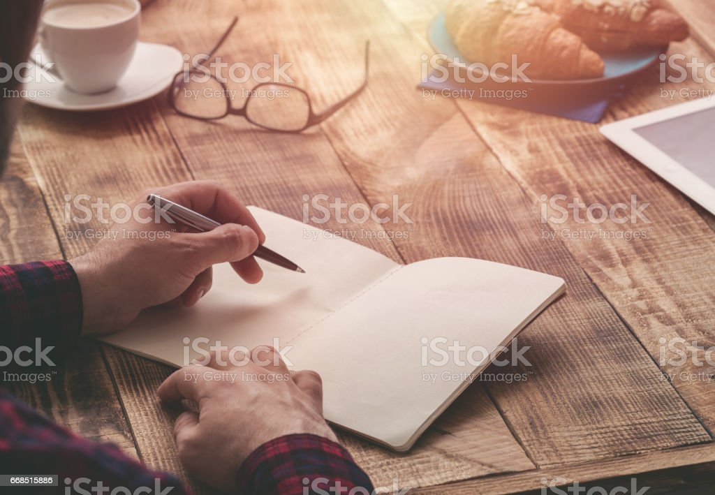 Man hand with pen writing on notebook on a wooden table stock photo